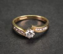 An 18ct gold and diamond-set ring, the central claw-set brilliant-cut diamond approximately 0.