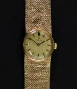 Omega; a lady's 9ct gold wristwatch, the circular textured gold dial, with baton indicators,