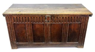 A late 17th century oak coffer, of panelled construction, the hinged top with gouged ends,