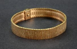 A 9ct yellow gold wide bracelet of textured stylized brick-link design,