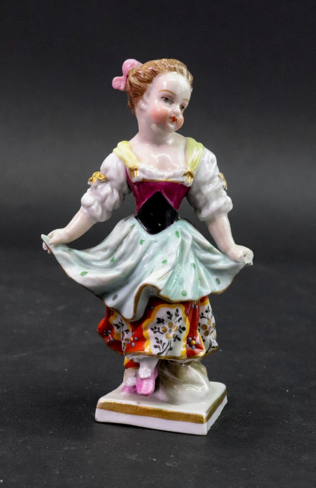 Lot 72 - A Sampson porcelain figure of a young girl, her hands gathering up her dress, 11cm high.