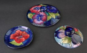 Two Moorcroft jar covers, Pansy and Wisteria Plum patterns,