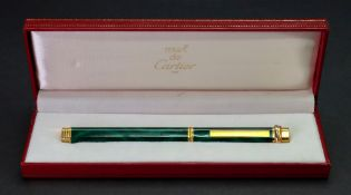 Must de Cartier Paris; a gold plated and green lacquer faux marble ball point pen, in fitted case.
