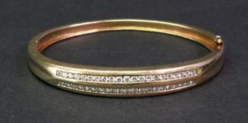 A diamond-set hinged yellow precious metal bangle of slightly tapered design,