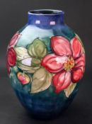 A Moorcroft Clematis pattern baluster vase, decorated against a blue/green ground, 27cm high.