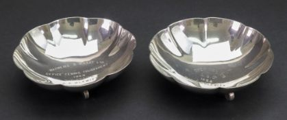 A pair of circular dishes, detailed sterling silver, with lobed and fluted sides, on three feet,