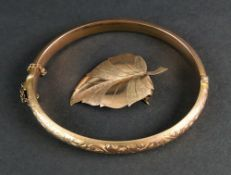 A 9ct rose gold hinged bangle, engraved with scrolling foliage,