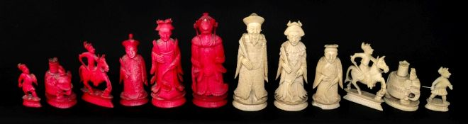 A Chinese carved ivory chess set, 19th century, one half stained red, the other natural, Kings 10.