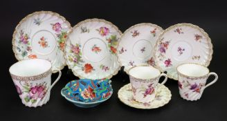 A Dresden large tea cup and pair of saucers, painted with bouquets and scattered flowers,
