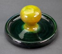 A Moorcroft green glazed paper weight, on a dished circular base, 16.5cm diameter.