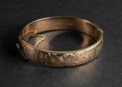 A 9ct gold hollow hinged bangle, of oval design, engraved with a repeat flowerhead motif,