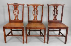 A set of six George III country Chippendale style oak and elm dining chairs,