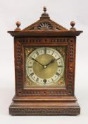 An Edwardian carved oak mantel timepiece