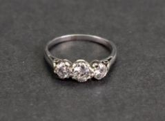 A three-stone diamond ring, the central