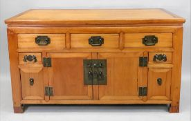 A Chinese sideboard, fitted with five drawers flanking a cupboard,