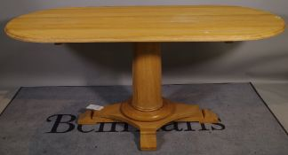 A 20th century oak oval dining table on turned column and quatrafoil base, 180cm wide x 77cm high.
