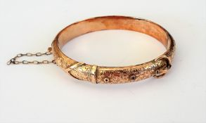 A 9ct gold oval hinged bangle, with foliate engraved decoration, on a snap clasp,