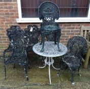 A set of four black painted metal garden chairs, with a matching oval metal garden table,