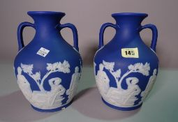 A pair of Wedgwood blue Jasper Ware twin handled vases, decorated with classical figures, 24cm tall.