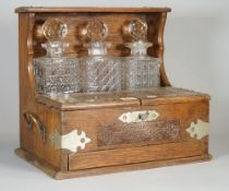 An early 20th century oak cased three division tantalus, 35cm wide x 32cm high.