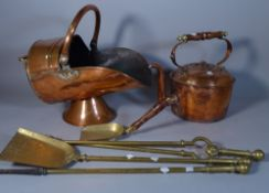 A 19th century copper helmet shaped coal scuttle, a large kettle and a set of brass fire tools, (5).