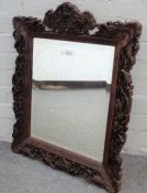 A Chinese hardwood mirror with extensively carved frame depicting hunting scenes,