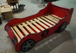 A 20th century single bed formed as a red race car with pull out bed beneath,