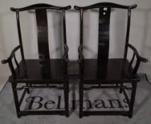 A pair of early 20th century ebonised Chinse open armchairs, 50cm wide x 94cm high (2).