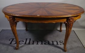 A 20th century walnut oval extending dining table, with inlaid sunburst decoration,