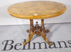 An Edwardian inlaid walnut oval centre table on four downswept supports, 89cm wide x 65cm high.