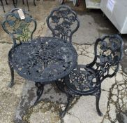 A set of three 20th century black painted cast iron garden chairs with rose decorated back and two