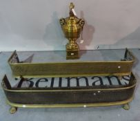A 20th century large urn shaped brass lamp base, 65cm tall, and two brass and steel fire fenders,