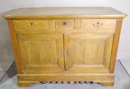 An early 20th century French Beech commode with three frieze drawers over cupboard base on bracket