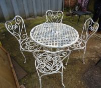 A set of four 20th century white painted metal garden armchairs with heart shaped backs and