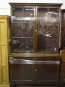 A George III style mahogany bookcase with pair of glass doors over cupboard, on bracket feet,