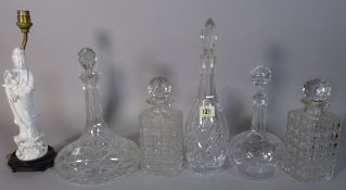 A group of ten assorted 20th century cut glass decanters and two blanc de chine style figures made