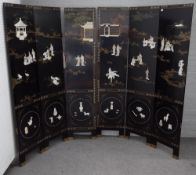 An early 20th century Chinese black lacquer six fold screen decorated in relief with