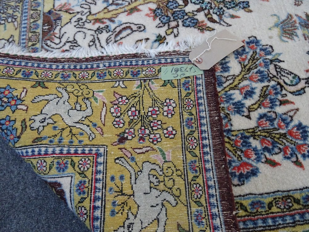 Lot 1539 - A part silk Qum rug, Persian, the ivory field with single flowering trees,