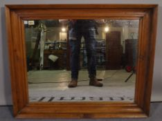 An early 20th century pine wall mirror with deep moulded frame and inset bevelled glass,