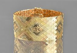A three colour gold bracelet, in a wide shaped link design, with partly facet cut decoration,