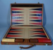 A 20th century brown leather cased travelling Backgammon set, 67cm wide.