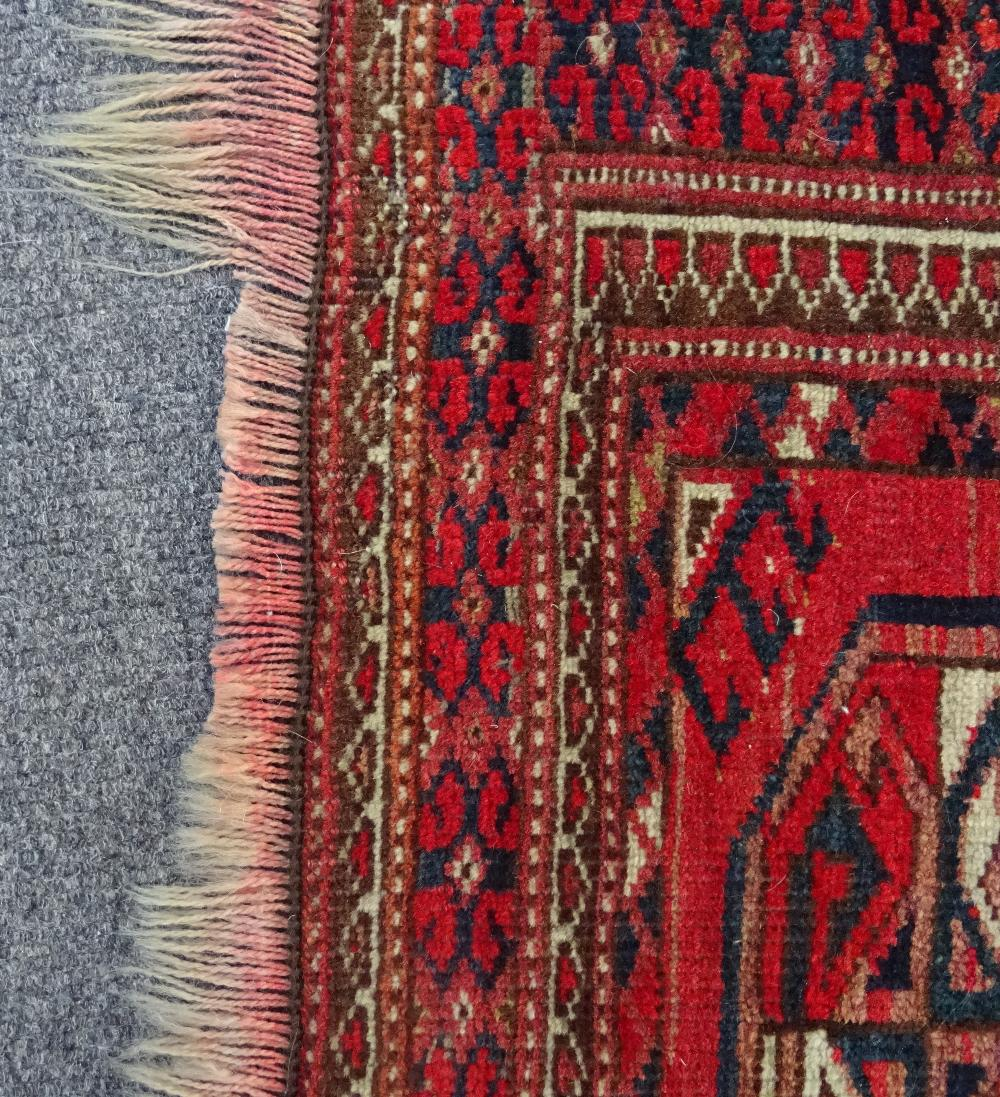 Lot 1535 - A large Afghan Turkman prayer rug, the madder mehrab with rows of guls, hooked supporting motifs,