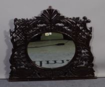 An 18th century carved wall mirror with oval mirror plate,