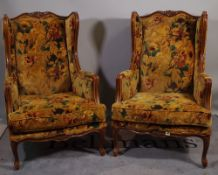 A pair of 20th century French stained beech wingback armchairs on cabriole supports,