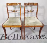 A set of four Regency style brass inlaid stained beech dining chairs on sabre supports,
