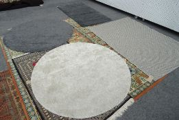A basket weave grey rug, 168cm x 118cm and two circular machine made rugs, 133cm diameter,