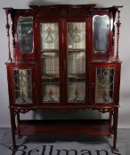 A late Victorian mahogany glazed display cabinet, with Art Nouveau stained glass motifs,