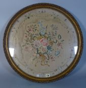 A 19th century circular needlework embroidery depicting a central bouquet of flowers,