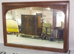 A large Victorian oak mirror, with arch plate and floral carved corner spandrels,