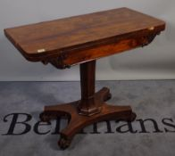 A 19th century rosewood rectangular foldover tea table, with turned column and quatrefoil base,